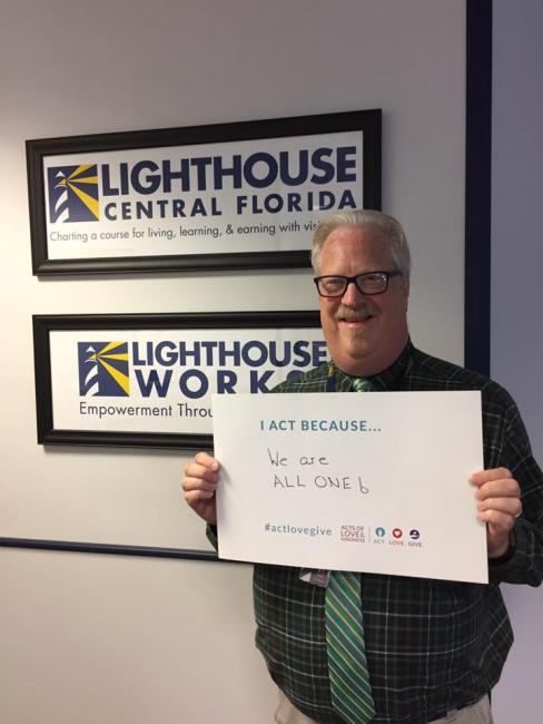An image of Todd at the Lighthouse Works office holding a sign that says 'We are all one'