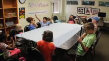 A group of elementary School age children gathered around a table raising their hands to answer a question in our School Age Children services program