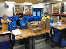 Image of three Lighthouse Works fulfillment specialists wearing facemasks and assembling care packages.