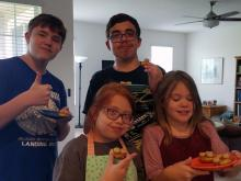 Lighthouse children's program student, Libby Lufkin, seen here sharing cookies with her two older brothers and her sister.