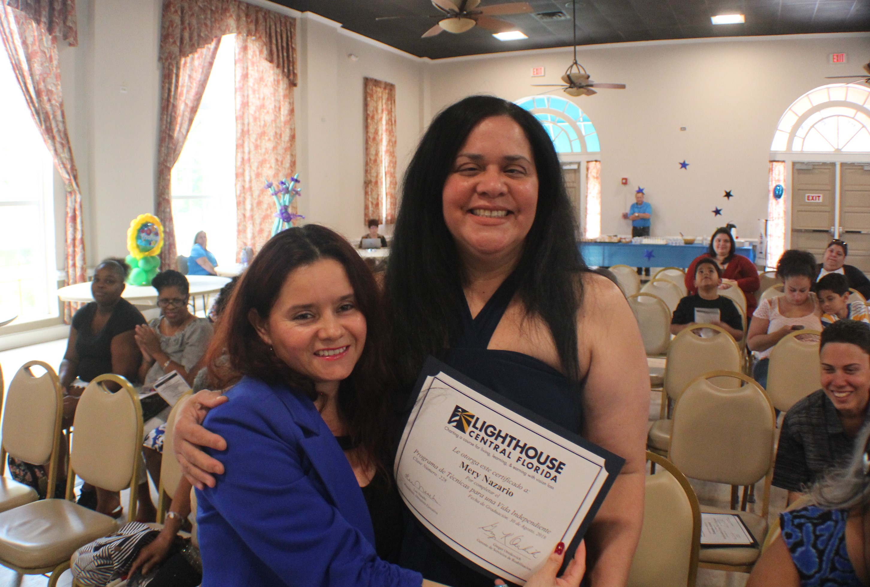 Lighthouse staffer, Maria [left] embraces graduate from recent Foundations of Daily Living course