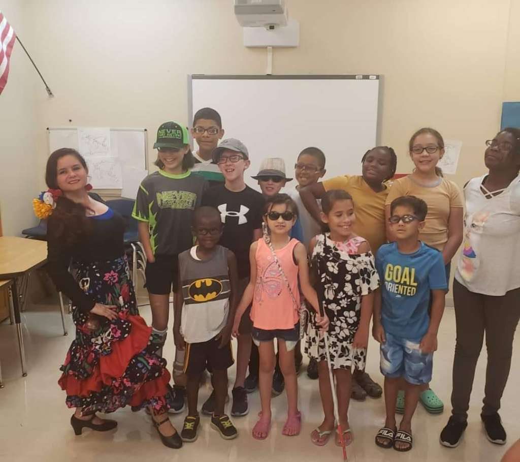 Lighthouse staffer, Maria [far left], poses with Lighthouse Academy students following a lesson on dance