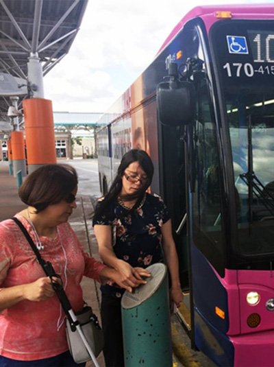 An Orientation Mobility Instructor walking a client through using a LYNX bus