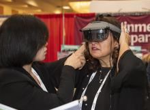 a woman who is visually impaired trying on a headset imaging device at the CSUN conference