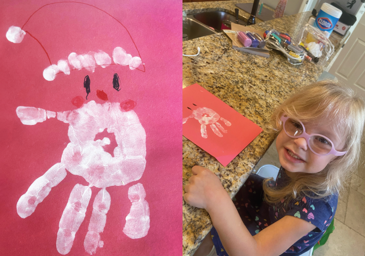 Maddalena smiling for the camera in her family's kitchen with her artwork depicting a Santa Claus on red construction paper with a palm print in white paint as his face and beard