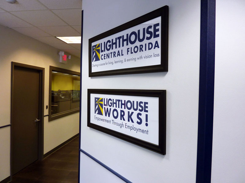 an image of a hallway leading into the Lighthouse Works building with the contact center on the left, and a wall  on the right with the Lighthouse Central Florida and Lighthouse Works logos on it