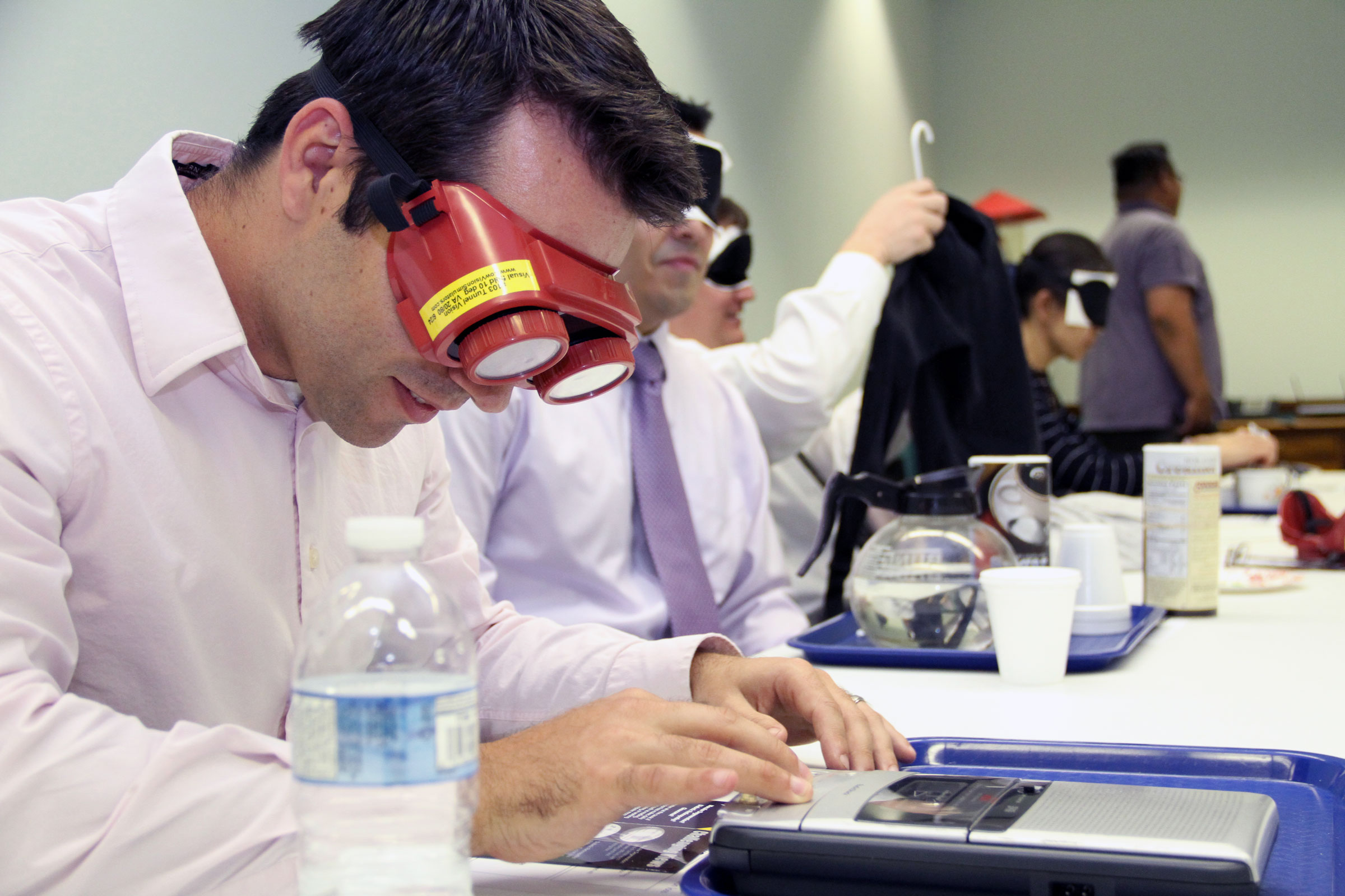 A group of attendees sitting at a table wearing blindfolds or low vision simulators attempting to do various daily living tasks