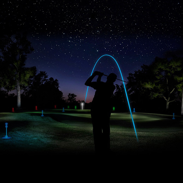 a golfer hitting a glowing ball from a tee at night