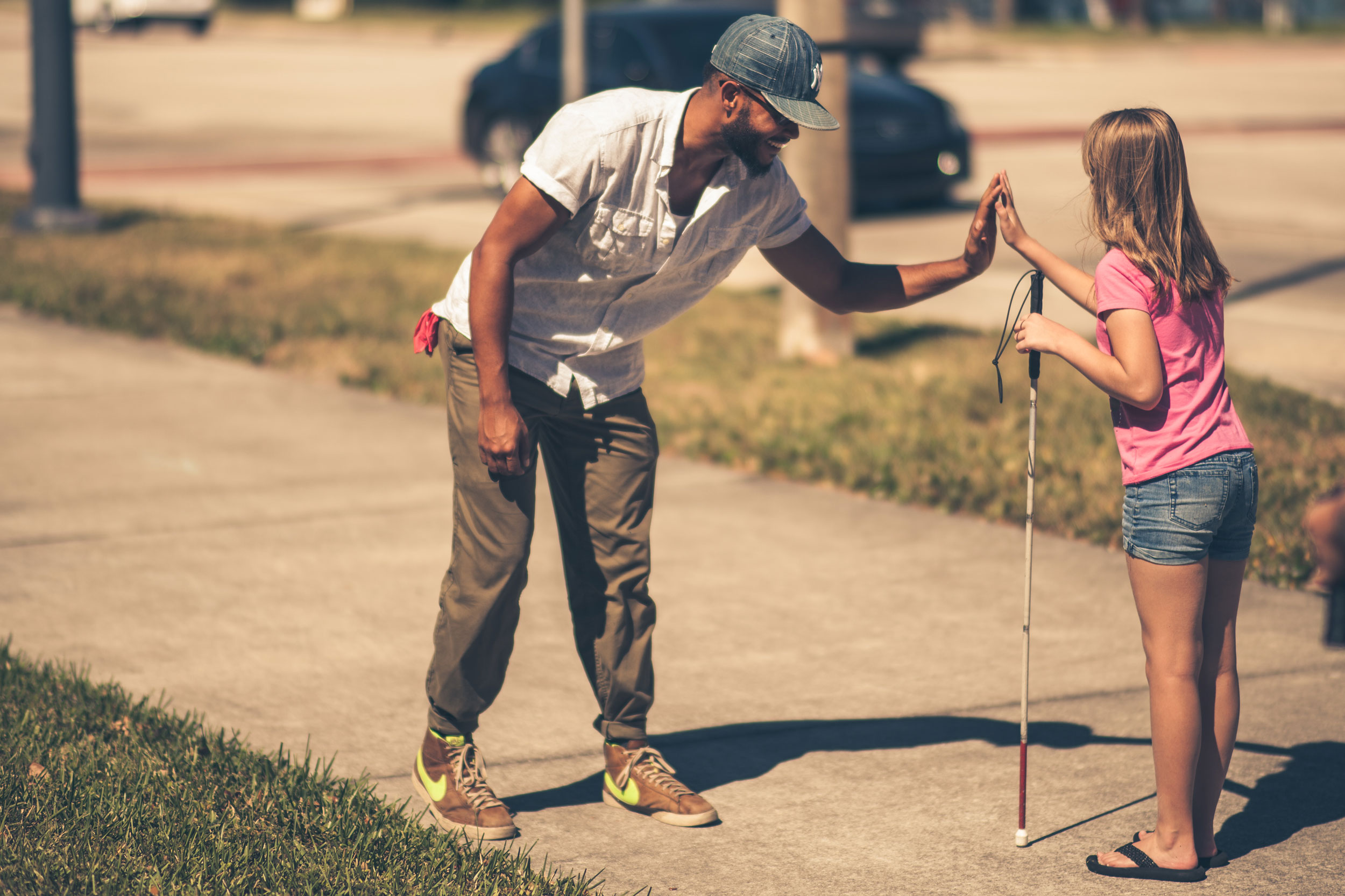 a child who is blind with a white cane in one hand and giving a high five with her other hadn to a person she is passing as she walks on a sidewalk