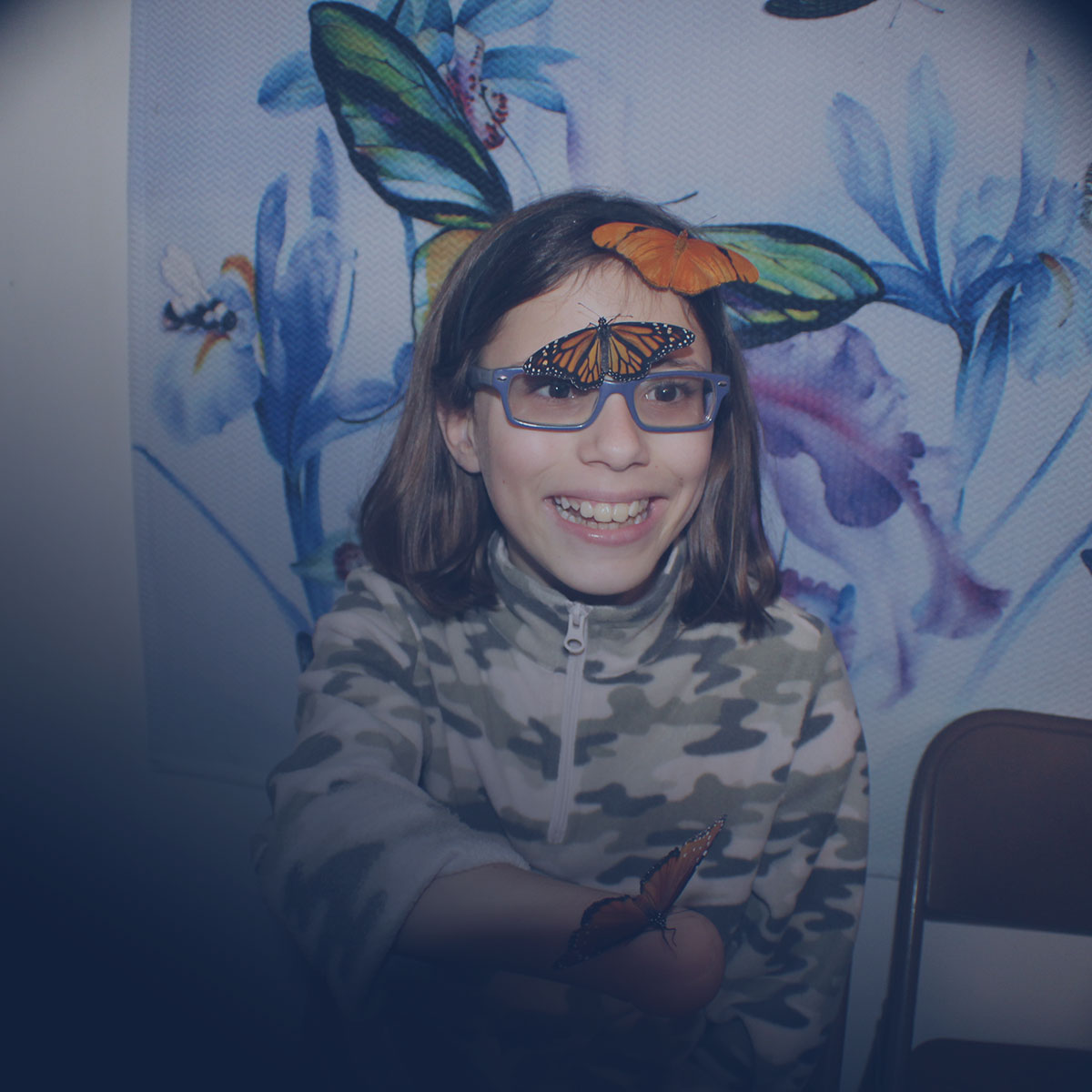 Image of Lighthouse client, Grace, interacting with butterflies on one of the student field trips to Butterfly Dan's